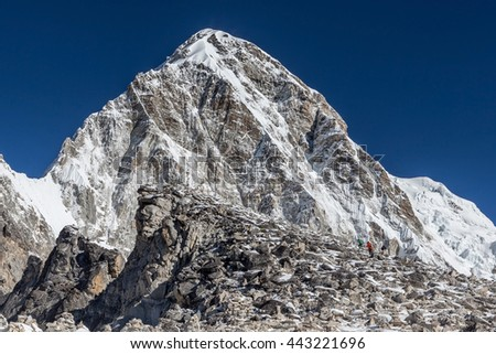 Trekkers coming up to Kala Patthar - the Everest mount view point - with Pumori mountain on the background. Trail leading up to the Kala Pattar hill near Everest Base Camp, Himalayas, Nepal. - stock photo