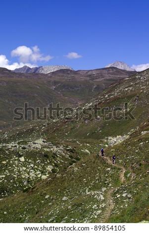 trekkers walking along a mountain path - stock photo