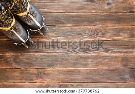 trekking shoes with crampons on dark wooden background, top view. Climbing equipment. Travel concept. - stock photo