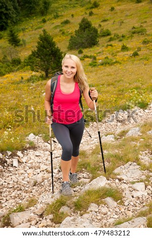Trekking - woman hiking in mountains on a calm summer day