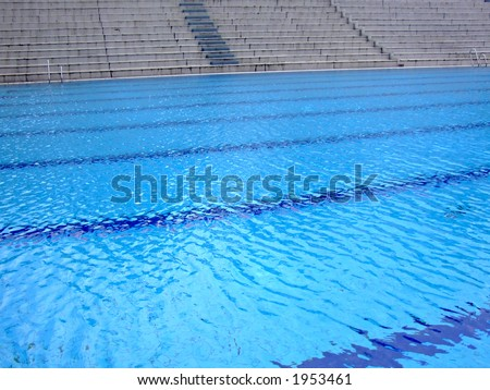 trembling surface of an olympic size swimming pool in empty sport arena