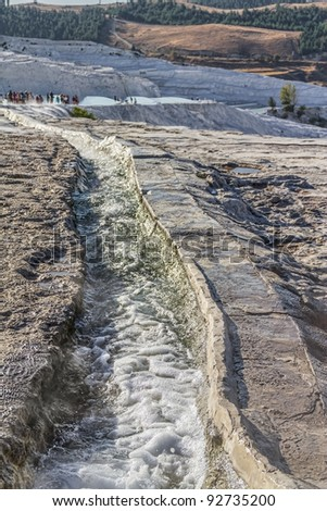 Trench with thermal water goes to the famous travertine terraces in Pamukkale (ancient Hierapolis), Anatolia, Turkye.
