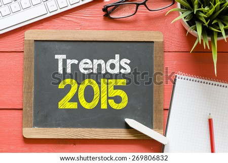 Trends 2015 handwritten on blackboard. Trends 2015 Handwritten with chalk on blackboard, keyboard,notebook,glasses and green plant on wooden background - stock photo