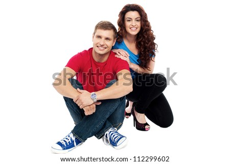 Trendy adorable love couple sitting on floor isolated against white background - stock photo