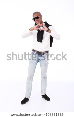 Trendy African American business man smiling with sunglasses,a silver bow tie, jeans,white shirt and black jersey, with his hands in the shape of a heart close to chest isolated on a white background