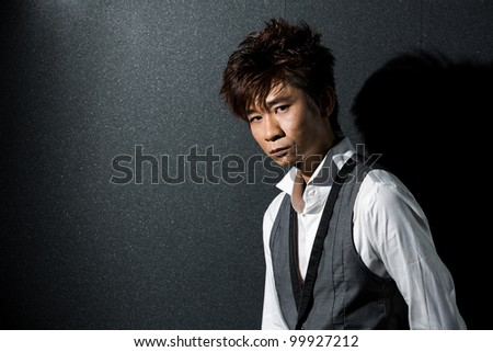 Trendy Asian man posing. Wearing a tuxedo and waistcoat.