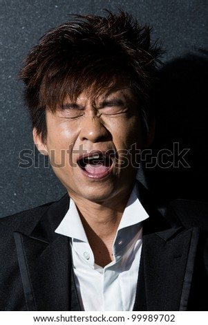 Trendy Asian man screaming. Wearing a tuxedo and waistcoat.
