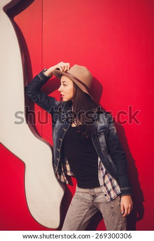 trendy beautiful brunette in posing on vivid wall background. Outdoors - stock photo