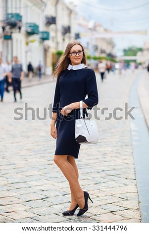 trendy beautiful girl posing in the street in the city