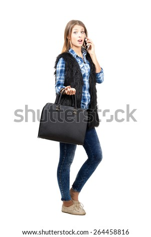 Trendy casual female fashion model surprised while talking on the smartphone.  Full body length portrait isolated over white background - stock photo