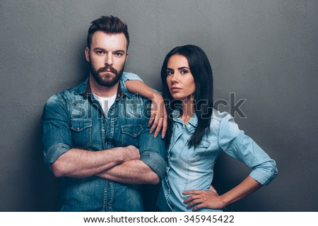 Trendy couple. Beautiful young couple in jeans wear standing close to each other and looking at camera with grey background - stock photo