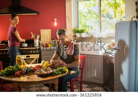 Trendy couple in casual clothes cooking vegetables from the market in a red kitchen. The woman is stirring the sauce in a white pan while the grey hair man is taking care of the fresh vegetables. - stock photo