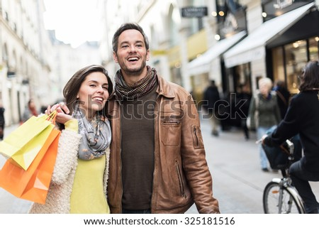 Trendy couple walking in a cobbled car-free street. The grey hair man with beard is wearing a brown leather coat and the woman a yellow top and two shopping bags, they also have scarfs - stock photo