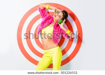 Trendy DJ girl in bright colorful clothes and headphones posing over red target. Party style. Fashion studio shot. - stock photo