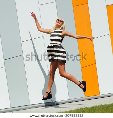 Trendy fashionable girl emotionally jumping on the background color of orange wall. outdoor urban life style - stock photo
