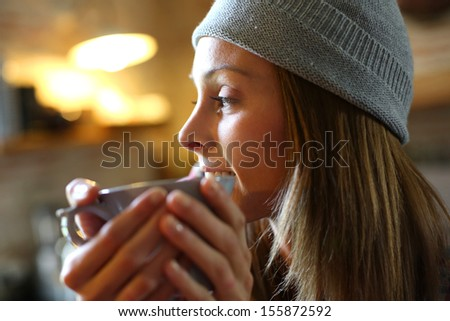 Trendy girl at home having hot drink - stock photo