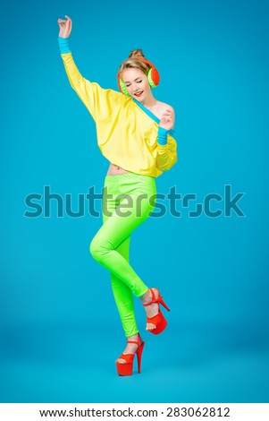 Trendy girl in bright colorful clothes listening to music in headphones and dancing. Party style. Fashion studio shot. - stock photo