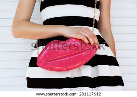 trendy girl in elegant striped dress with pink lacquered clutch in her hands. Outdoor shot - stock photo