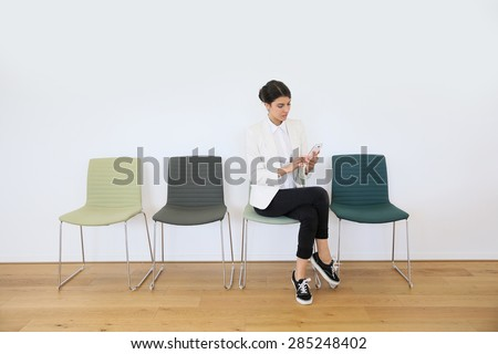 trendy girl in waiting room sending message with smartphone - stock photo