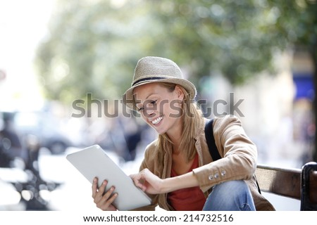 Trendy girl using tablet sitting on bench in town - stock photo