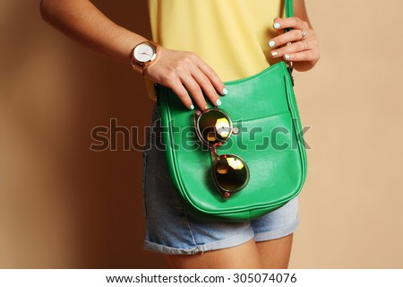 Trendy girl with green handbag clutch and sunglasses , fashion gold watch. Summer spring outfit  - stock photo