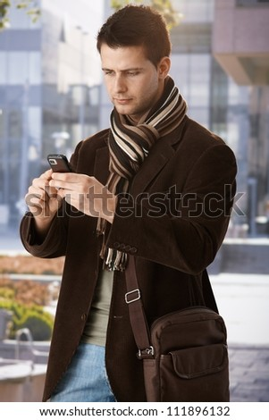 Trendy guy texting on mobile phone, standing outside of building in sun. - stock photo