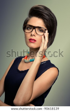 Trendy hairstyle and glasses for a young vintage woman, studio shot - stock photo
