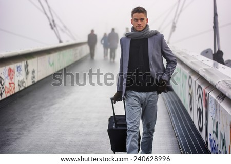 Trendy handsome man walking across a bridge on a misty cold day pulling a suitcase behind him as he departs on a trip