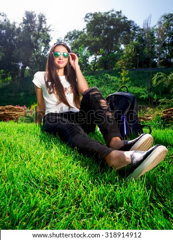 Trendy Hipster Girl Relaxing on the Grass.Modern Youth Lifestyle Concept.Summer girl in grass smiling happy.Full length portrait of stylish young woman lying in park on sunny sunshine day.