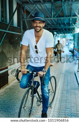 Trendy hipster guy riding on bicycle on street, smiling.