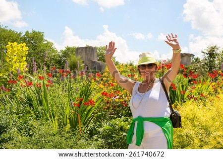 Trendy joyful Grandma outdoors in her garden laughing and waving her hands in the air in front of a bed of colorful summer flowers - stock photo
