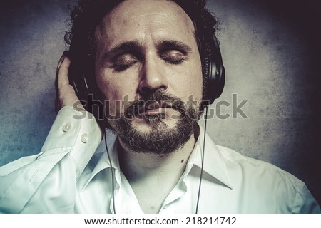 Trendy, listening and enjoying music with headphones, man in white shirt with funny expressions - stock photo