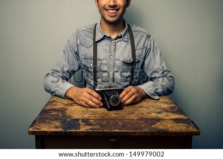 Trendy man with vintage camera at old desk - stock photo