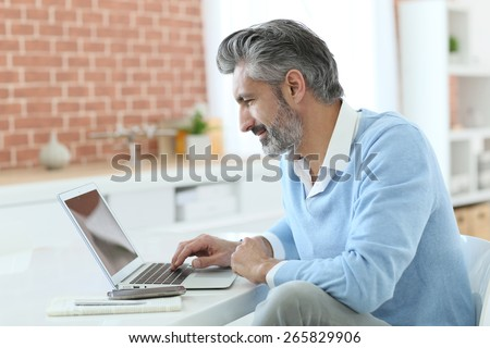 Trendy mature man working from home with laptop - stock photo