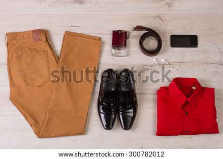 Trendy men's set of clothes and accessories on a wooden background. - stock photo