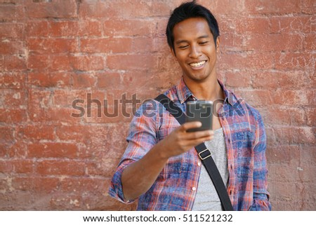 Trendy mixed-race guy standing by brick wall using smartphone