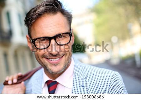 Trendy smiling guy walking in the street - stock photo