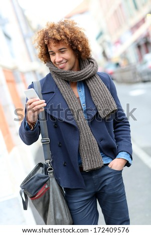 Trendy smiling man talking on phone in the street - stock photo