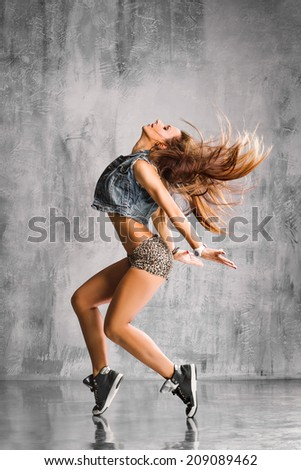 trendy street style dancer jumping on studio background - stock photo