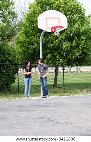 trendy teen girl and guy talking outside - stock photo