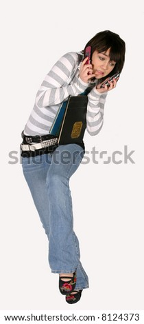 trendy teen girl trying to hold books and 2 cell phones - stock photo