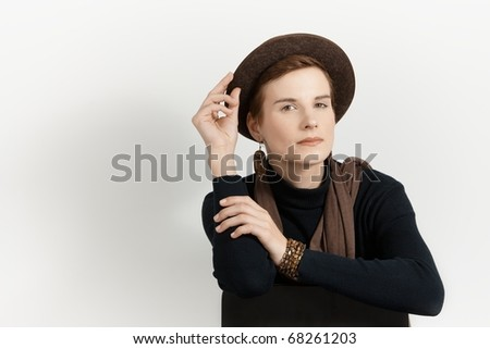Trendy woman posing on chair, holding hat, smiling at camera.?