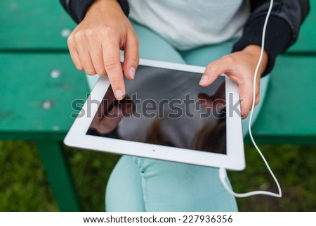 Trendy woman with Tablet PC wearing headphones outdoors - stock photo
