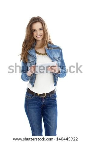 Trendy young female student with a tablet-pc dressed in a denim jacket and jeans standing facing the camera and smiling, on white