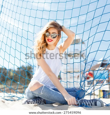 Trendy young girl posing against a background of blue football goal on a beach in the summer at the sea in sunglasses. - stock photo