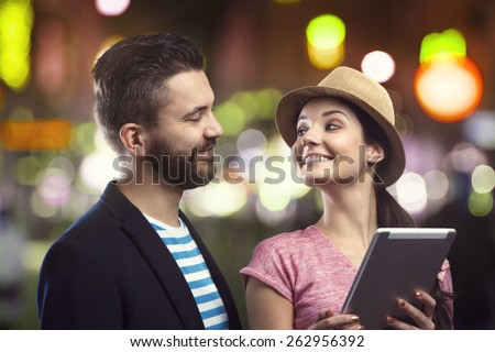 Trendy young hipster couple with a tablet enjoying nightlife in the city