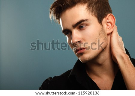 Trendy young man in black shirt, portrait of sexy fashion boy looking right over dark blue - stock photo