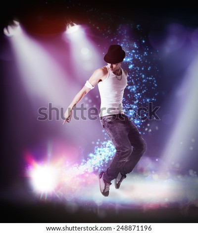 Trendy young man in hat hip hop dancing, breakdancing on a stage, in the beams of three spotlights leaping in the air with bent knees - stock photo