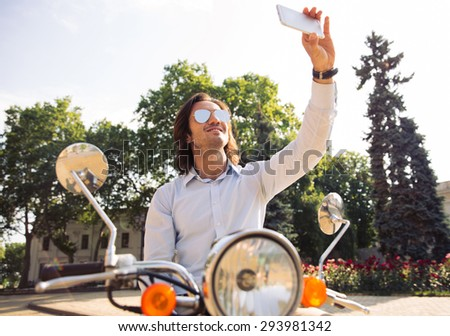 Trendy young man on scooter making selfie photo on smartphone in old european town - stock photo
