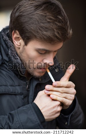 Trendy young man smoking cigarette. Closeup portrait of man standing outside - stock photo